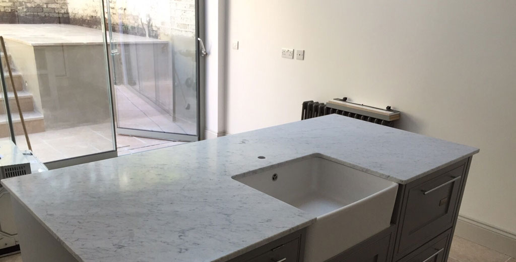 Kitchen Island in Bianco Carrara honed marble for a residence in Chiswick by My Kitchen Worktop